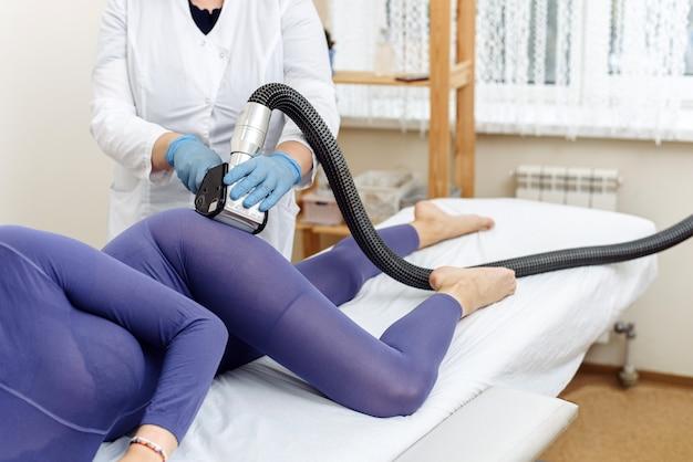 미용사는 보라색 옷을 입은 젊은 여성의 엉덩이에 lpg 마사지를 합니다.