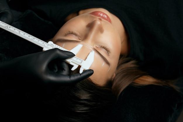 エステティシャンは、美容院でスタイリッシュなブルネットの女性に額のマイクロブレードの前に測定を行います。上面図