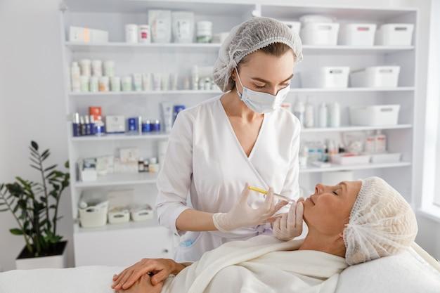 Косметолог делает уколы мезотерапии пожилой женщине.