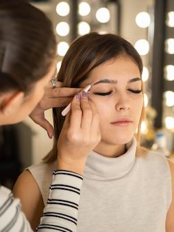 Косметолог делает микроблейдинг бровей молодой женщине