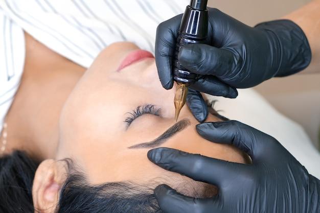 Косметолог делает перманентный макияж бровей на лице красивой молодой женщины