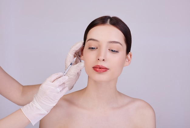Beautician makes procedures for face injections of a young woman.