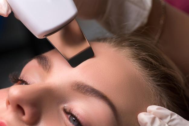 Косметолог производит ультразвуковую чистку лица. аппаратная косметология. фото крупным планом.