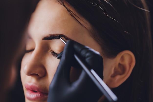 Косметолог-визажист наносит краску хны на ранее выщипанные, дизайнерские, подстриженные брови в салоне красоты при коррекции сеанса. профессиональный уход за лицом.