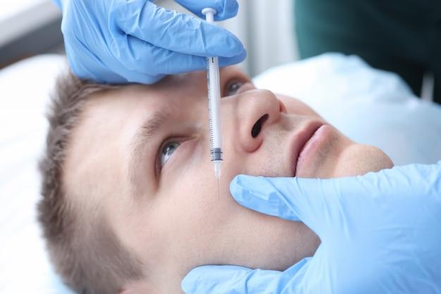 男性患者の顔に注射をする美容師。美容医学の概念