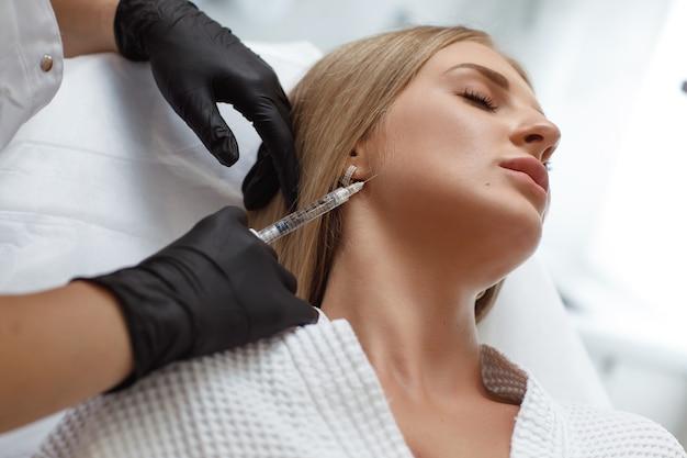 Beautician making injection in woman's face, closeup. biorevitalization procedure. plastic surgery. cosmetology salon