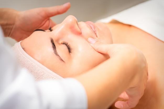 Косметолог делает лимфодренажный массаж лица или подтяжку лица в салоне красоты.