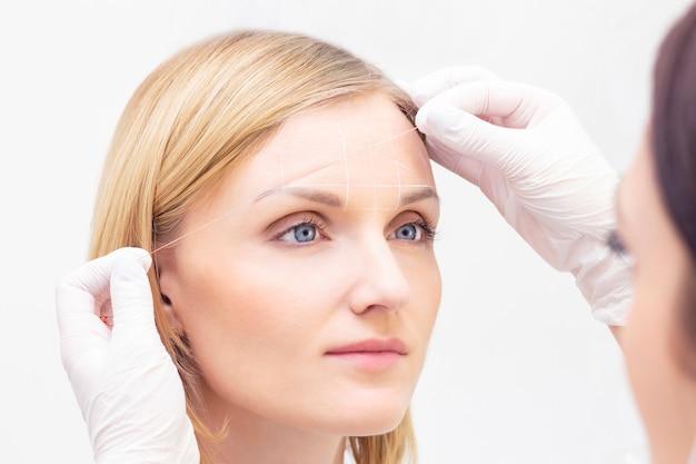 美容師は、眉毛の入れ墨の糸の助けを借りて眉毛に印を付けます