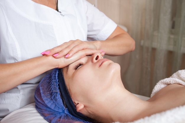 Beautician massages the face of client