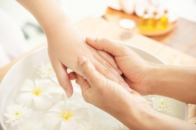 女性スパサロンクライアントの手をマッサージするエステティシャン。女性の足と手のスパのためのスパトリートメントと製品。