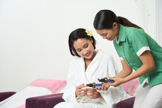 Beautician offering different cream to client