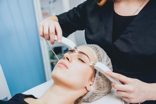 Beautician and the patient in the clinic of aesthetic medicine receiving a treatment