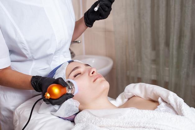 Косметолог проводит процедуру электропорации на клиенте
