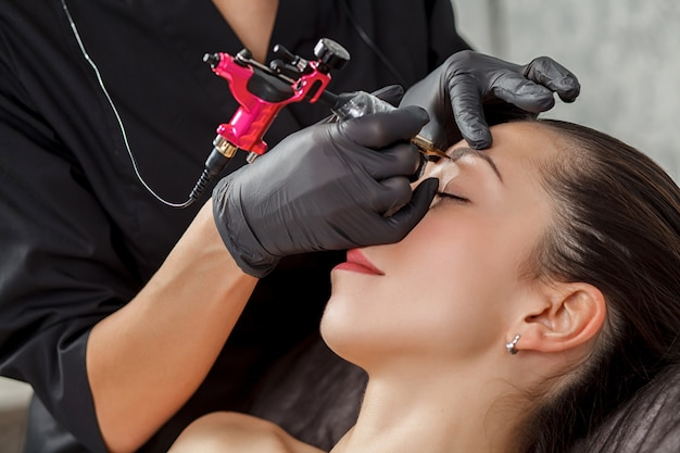Beautician performs modeling permanent eyebrows