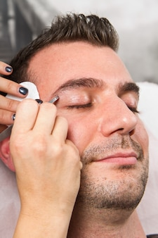 Beautician plucking a beautiful man eyebrows with tweezers in a beauty salon