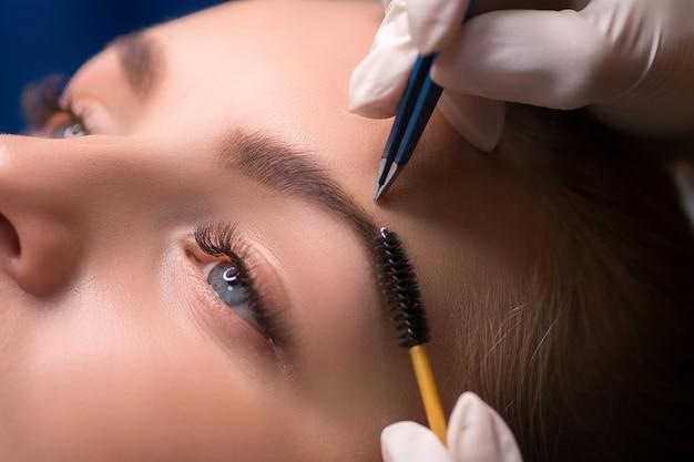 眉毛を摘む美容師。ビューティーサロンでの眉毛ケア。