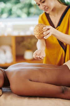Beautician pouring massage oil on back of female client before giving her relaxing spa treatment
