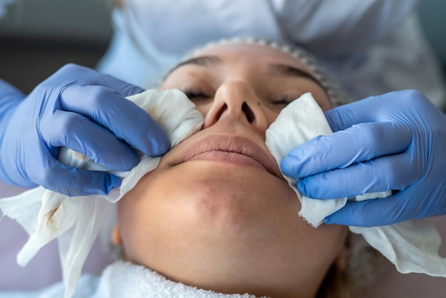 Beautician prepares a woman for the procedure and clean face skin with cotton pad
