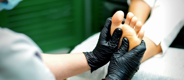 Beautician in protective rubber gloves doing massage on the sole of the female foot in a spa beauty salon