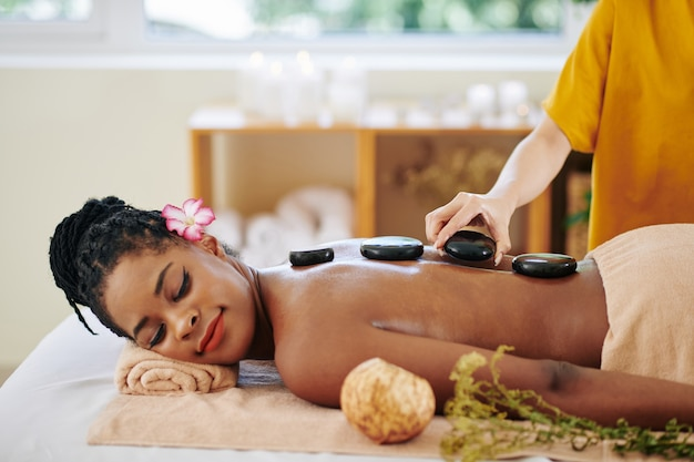 Beautician putting hot basalt stones along the spine of relaxed pretty young black woman