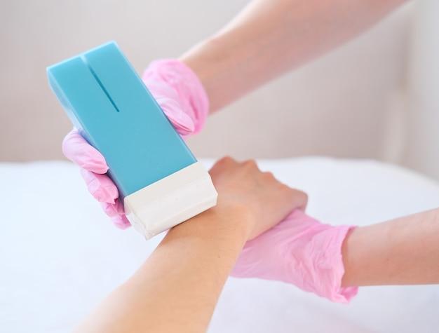 美容師はワックスで髪を削除します。脱毛と砂糖漬け。手袋で女性の手。スパのコンセプト