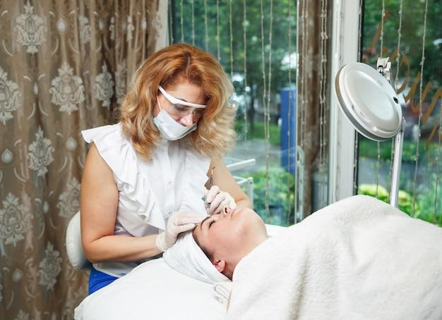 美容師が削除-ビューティーサロンで若い美しい女性の顔からにきびを絞ります。
