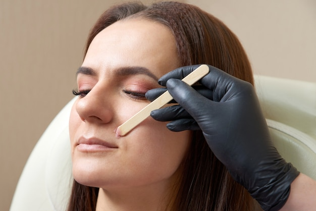 Beautician removing hair above upper lip of young woman in salon. mustache depilation