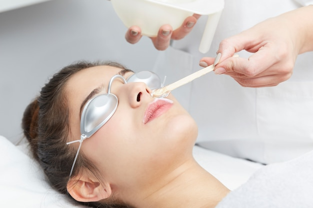Beautician removing hair of young woman with laser