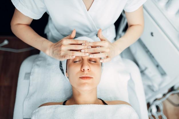 美容師が女性患者の顔にクリームをこすり