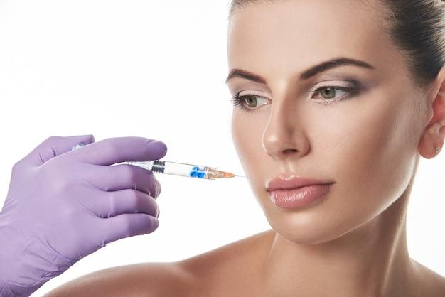 美しい女性の顔の近くに注射器を保持しているパープルグローブの美容師の手