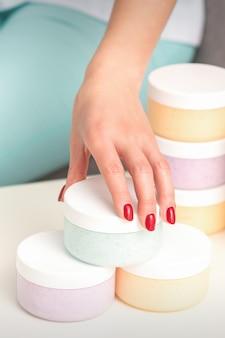 미용사의 손은 화장품, 보습 크림, 왁스 페이스트를 제공하고 판매하는 테이블에서 화장품과 함께 항아리를 가져옵니다.
