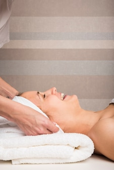 Beautician's hand wrapping towel on smiling young woman's head