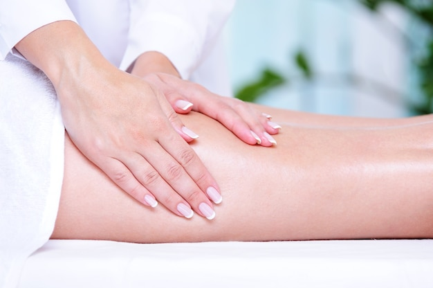 Beautician's hands doing massage for the female leg