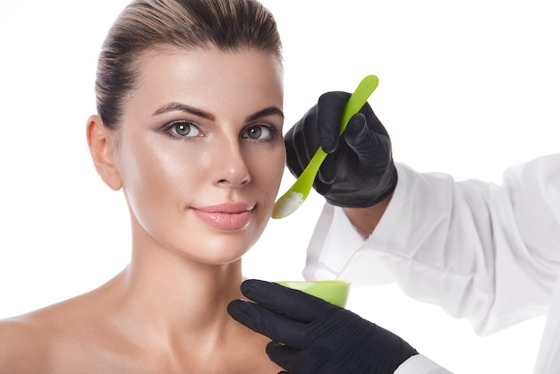 Beautician's hands holding green spatula and bowl with white beauty product
