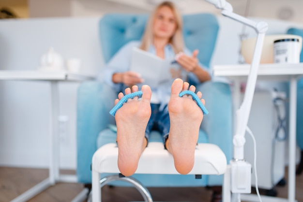 Beautician salon, foot care procedure. legs treatment for female client in beauty shop, customer sitting in armchair, relaxation before pedicure