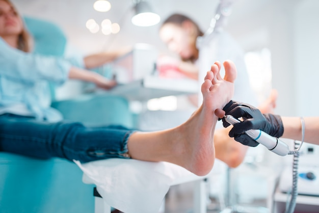 Beautician salon, foot polish procedure. legs care treatment for female client in beauty shop, master in gloves works with customer, relaxation
