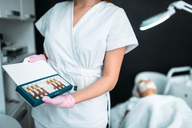 Косметолог показывает ампулы, препарат для омоложения
