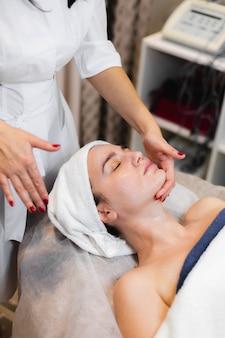 L'estetista in un salone di bellezza termale applica la crema sul viso di un cliente, una ragazza si trova su un tavolo di cosmetologia