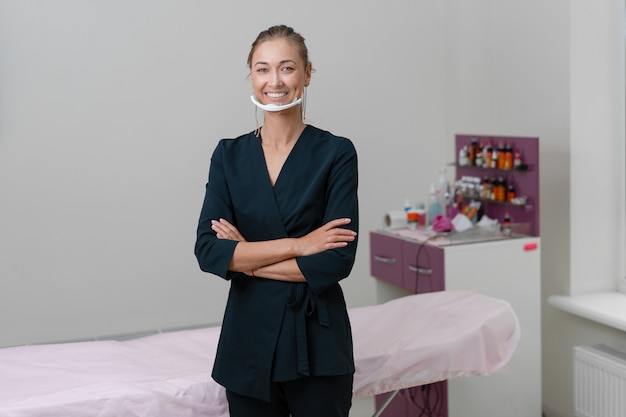 Beautician stands in mask and smiles.