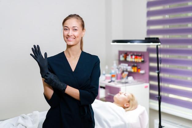 Косметолог стоит, надевает черные перчатки на руку и улыбается.