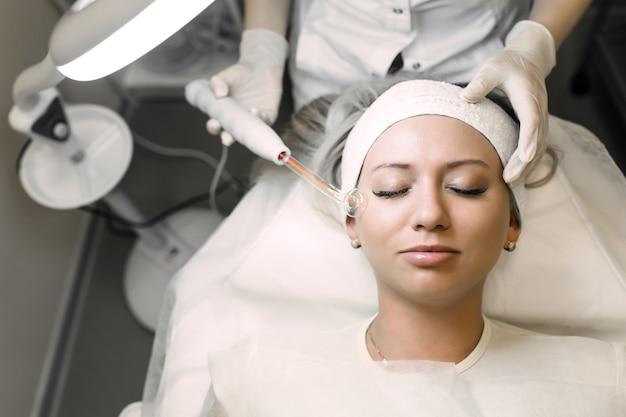 Косметолог, использующий электроинструмент для очистки кожи пациента