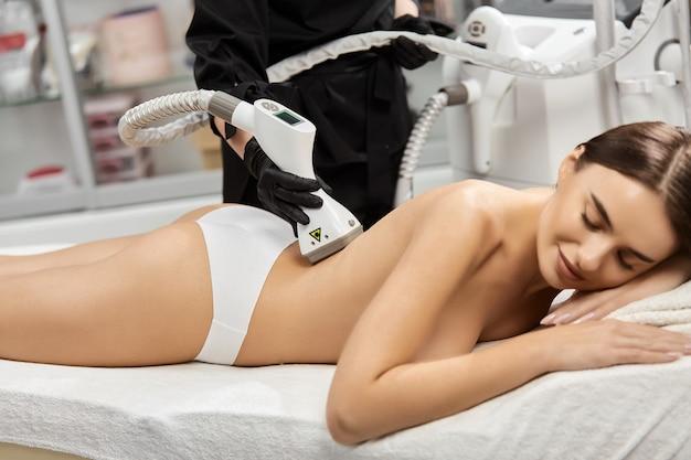Косметолог, использующий эндосферный массажер на спине женщины в салоне красоты