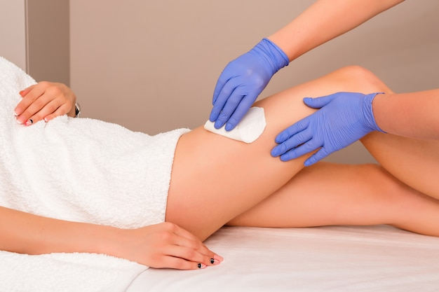 Beautician waxing female legs in spa center. removing unnecessary hair on the legs.