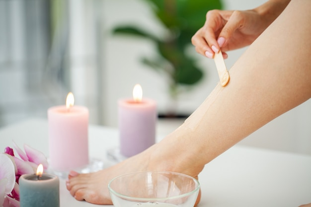 Beautician waxing female legs in spa center.