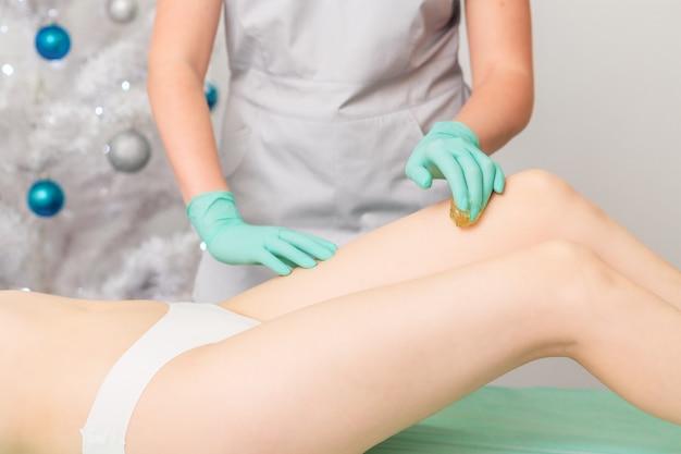 Beautician waxing legs of woman.