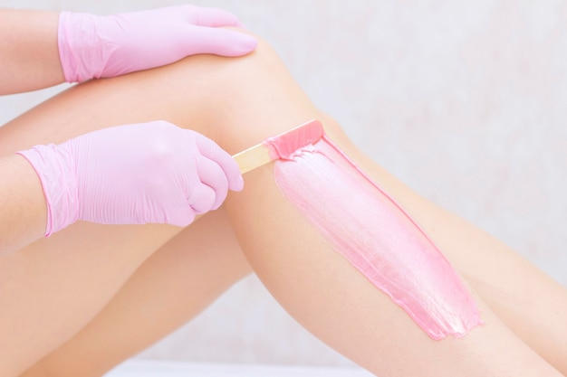 Beautician waxing legs of a young woman with pink wax in a spa center