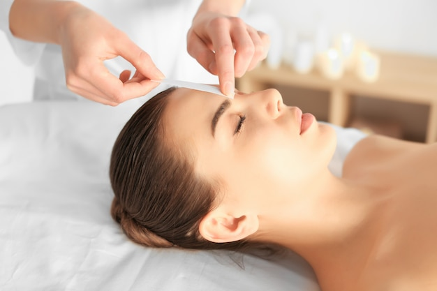 Beautician waxing young woman's eyebrows in spa center