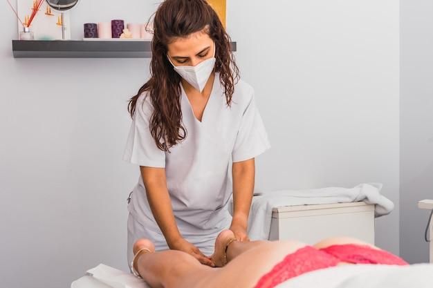 뷰티 스파에서 성인 여성에게 발 마사지를 해주는 얼굴 마스크를 쓴 미용사.