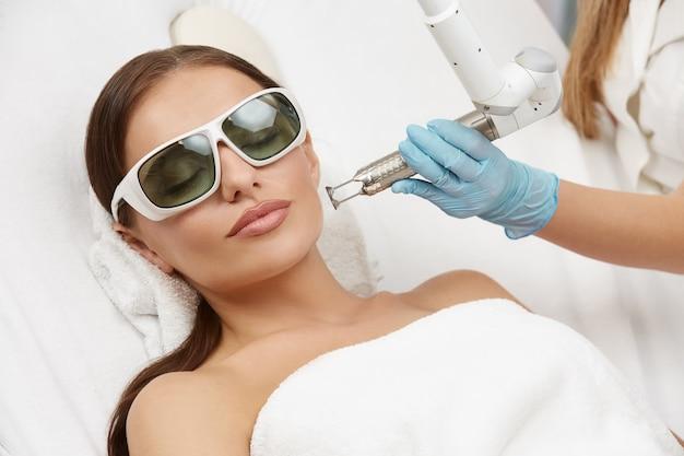 미용사 장갑을 끼고 뷰티 살롱에서 보호 안경으로 누워있는 아름다운 여성 근처에 레이저를 들고, 스파에서 얼굴 치료를받는 여성