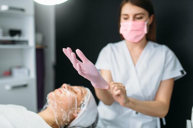 Косметолог носит перчатки, пациент с маской для лица